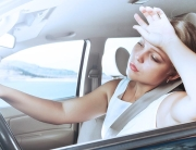 woman driving car, holding hand to forehead